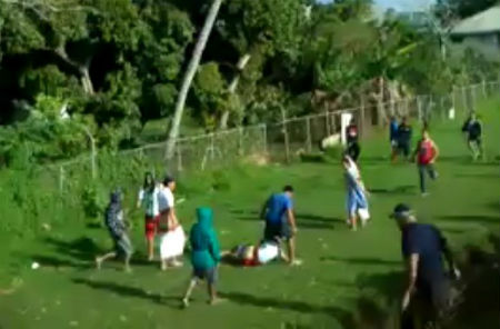 The teenage boy who was beaten by the Tongan police officer is standing, while a Tonga College student lies face down on the ground.